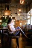 Усаживание женского фото модельное на кафе с ногами дальше подпирает стула, носящ этнические джинсы Стоковые Изображения RF