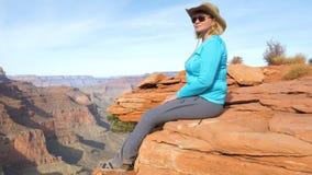 Усаживание женщины туристское на утесе качая ее ноги, и восхищает гранд-каньон взглядов стоковое фото