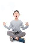 Усаживание и клекот мальчика над белизной Стоковая Фотография RF