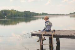 Усаживание и рыбная ловля мальчика от дока Стоковые Изображения