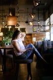 Усаживание кавказского фото модельное на кафе с ногами дальше подпирает стула, носящ этнические джинсы Стоковая Фотография
