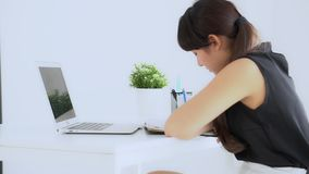 Усаживание красивой молодой азиатской женщины усмехаясь в исследовании живущей комнаты и учить пишущ тетрадь и дневник дома сток-видео