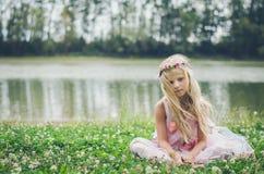 Усаживание маленькой симпатичной девушки унылое и одно в траве рекой Стоковое фото RF