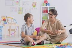 Усаживание мальчика и терапевта Стоковые Изображения