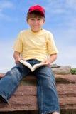 усаживание мальчика книги Стоковые Изображения RF