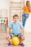 усаживание мальчика шарика гимнастическое Стоковые Фотографии RF