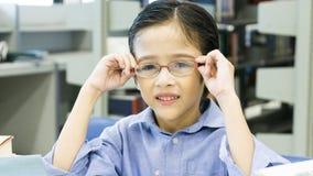 Усаживание мальчика Smiley смешное милое и держит eyeglasses на fac Стоковое фото RF