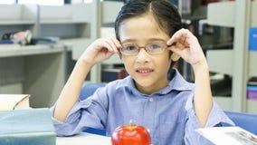 Усаживание мальчика Smiley смешное милое и держит eyeglasses Стоковое Фото