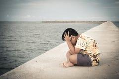 Усаживание мальчика несчастное самостоятельно на мосте Стоковые Изображения RF