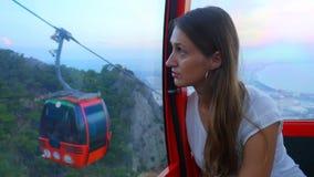 Усаживание молодой женщины туристское в фуникулере пока двигающ вниз сток-видео