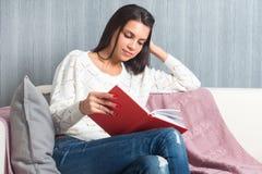 Усаживание молодой женщины прочитало софу кресла книги дома Стоковые Изображения