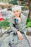 Усаживание очаровательной пожилой женщины старшее в стуле в саде Стоковое Фото