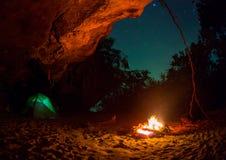 Усаживание пар располагаясь лагерем автомобиля шатра романтичное сельской местностью ночи костра Стоковая Фотография