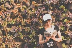 Усаживание подростка женщины битника наслаждается книгой чтения на пристани Концепция книги чтения молодой женщины, ретро тонизир Стоковая Фотография