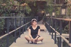 Усаживание подростка женщины битника наслаждается книгой чтения на пристани Youn Стоковые Фотографии RF
