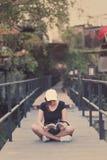 Усаживание подростка женщины битника наслаждается книгой чтения на пристани Youn Стоковые Фото