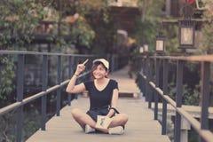 Усаживание подростка женщины битника наслаждается книгой чтения на пристани Youn Стоковая Фотография RF
