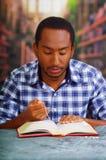 Усаживание религиозного человека пока держащ розарий, молящ и читающ от открытой книги на столе в фронте, концепции вероисповедан Стоковая Фотография RF