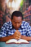 Усаживание религиозного человека пока держащ розарий, молящ и читающ от открытой книги на столе в фронте, концепции вероисповедан Стоковые Фото