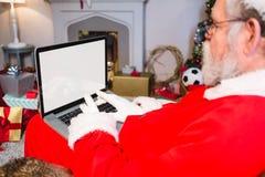 Усаживание Санта Клауса и компьтер-книжка использования Стоковое фото RF