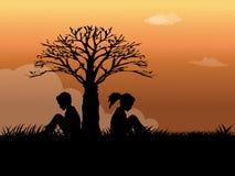 усаживание травы девушки мальчика Стоковое Фото