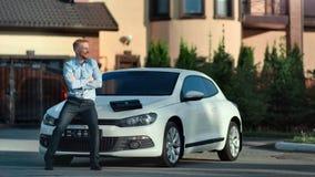 Усаживание успешного молодого европейского парня смеясь на bonnet автомобиля на предпосылке дома задворк сток-видео