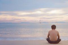 Усаживание человека видит море самостоятельно Стоковые Изображения
