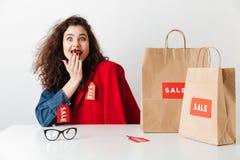 Усаживание excited радостной девушки shopaholic с бумажными хозяйственными сумками Стоковые Фото