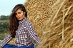 усаживание haystack девушки страны Стоковые Изображения