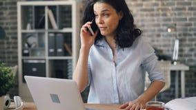 Усиленная девушка споря на мобильном телефоне в офисе обсуждая проблемы работы видеоматериал