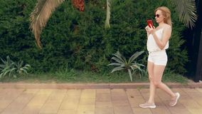 Усиленная женщина говоря на телефоне на улице, имеющ слабонервную боль переговора, чувствовать и головную боль steadicam сток-видео