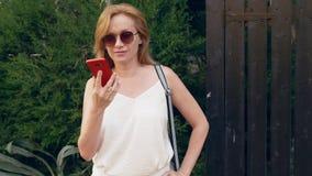 Усиленная женщина говоря на телефоне на улице, имеющ слабонервную боль переговора, чувствовать и головную боль steadicam видеоматериал