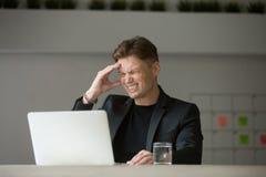 Усиленный бизнесмен чувствует, что мигрень головной боли работает на компьтер-книжке a Стоковые Фотографии RF