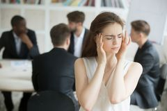 Усиленный женский корпоративный работник имея мигрень во время briefi Стоковое Изображение