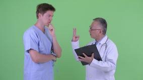 Усиленный зрелый японский доктор человека с пациентом молодого человека получая плохую новость совместно сток-видео