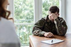 Усиленный и несчастный солдат в зеленой форме во время назначения с psychotherapist стоковая фотография rf