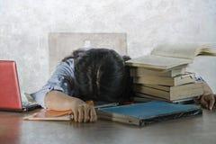 Усиленный и разочарованный студент подростка работая с учебниками и ноутбуком на полагаться стола сокрушанный и вымотанный дальше стоковые изображения rf