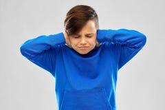 Усиленный мальчик в ушах голубого свитера закрывая руками стоковое фото