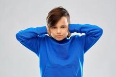 Усиленный мальчик в ушах голубого свитера закрывая руками стоковое изображение rf