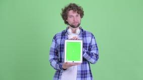 Усиленный молодой бородатый человек хипстера показывая цифровой планшет и получая плохую новость акции видеоматериалы