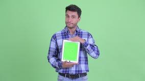 Усиленный молодой испанский человек показывая цифровой планшет сток-видео