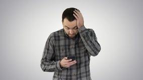 Усиленный молодой сотрясенный человек удивленным, страшить и нарушенным, чего он видит на его сотовом телефоне на предпосылке гра стоковое фото rf