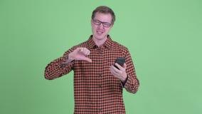 Усиленный молодой человек хипстера используя телефон и давать большие пальцы руки вниз сток-видео
