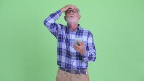Усиленный старший бородатый человек хипстера используя телефон и плохую новость получать сток-видео