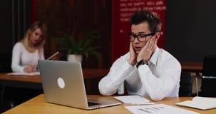 Усилие на работе Молодой бизнесмен смотрит очень утомленную работу в офисе с компьтер-книжкой Дело, люди, обработка документов и видеоматериал