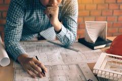 Усильте человека архитектора смотря светокопию на столе о str проблемы Стоковая Фотография RF