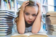 Усиленная девушка с головой в руке на школьной библиотеке стоковые фотографии rf