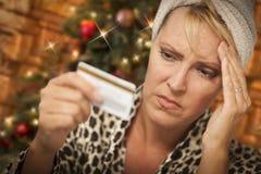Усиленная женщина держа кредитную карточку перед рождественской елкой стоковое изображение