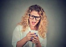 Усиленная женщина держа мобильный телефон сумашедший на напряжённых текстах и звонках Стоковое Фото