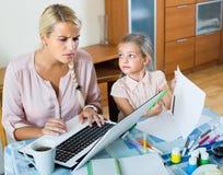 Усиленная женщина при ребенок работая от дома Стоковые Фотографии RF
